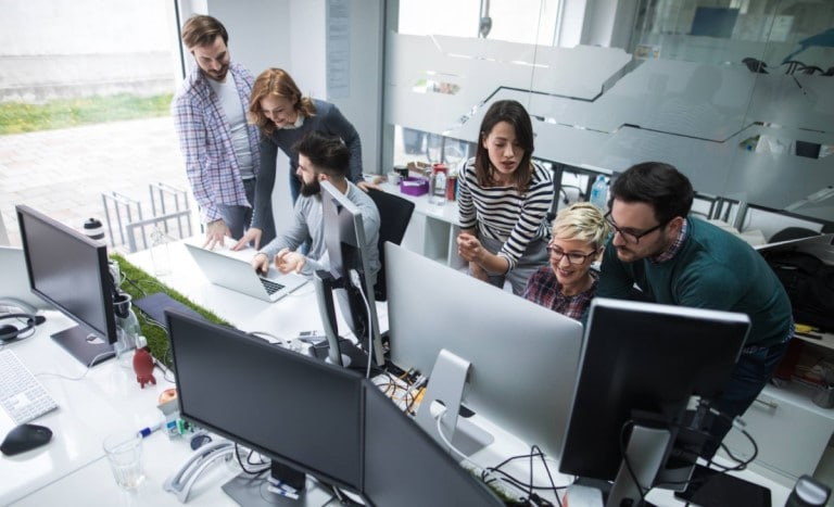 Digital transformation of work. Team working in office iwth computers.